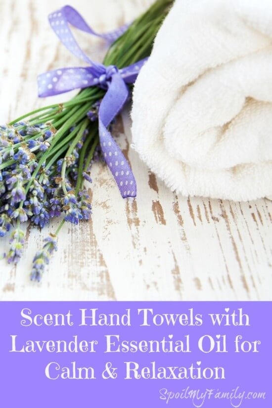 Bundle of lavender tied with a pretty purple polka dotted ribbon laying next to a white spa towel