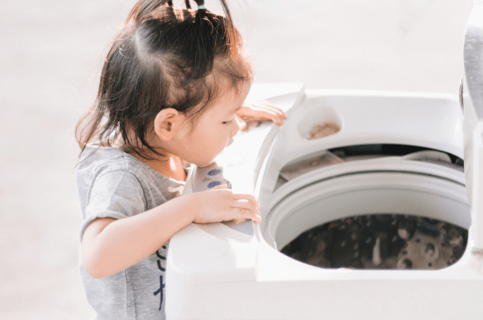 Young child peering into clothes washer