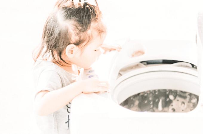 Little girl peering into washing machine