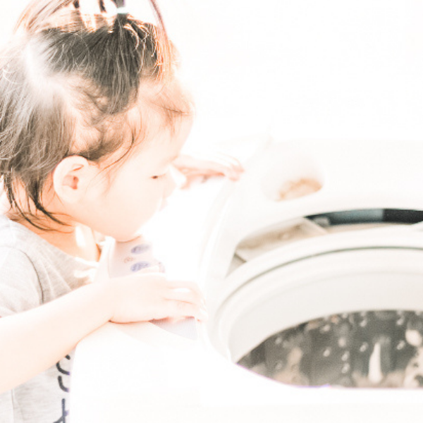 Little girl peering into washing machine