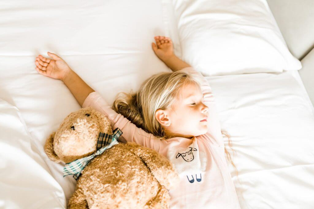 Young girl in pink pajamas asleep in bed with teddy bear.
