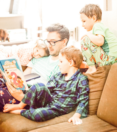 image of a father reading out loud to his attentive children