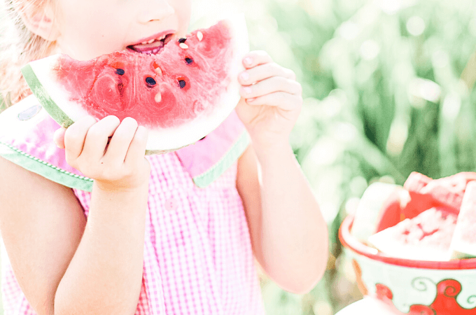 picture of cute little girl in pink dress eating watermelon in summer to represent summer solstice traditions and fun