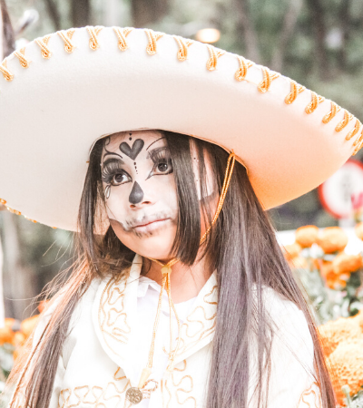 photo of young girl in dia del muertos makeup and sombrero - evocative of Mexican culture