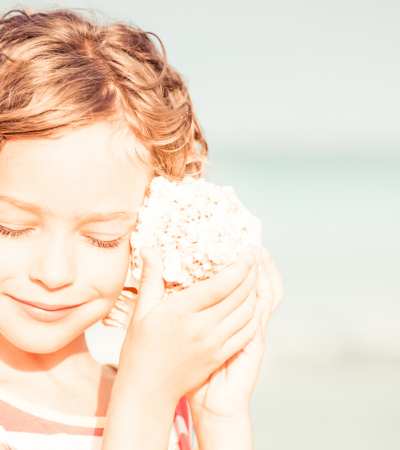Girl Holding Shell to Ear at the Beach