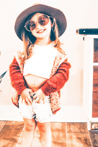 "Happy little girl in fun clothing and big sunglasses demonstrating a ""can do"" attitude or a growth mindset in kids"