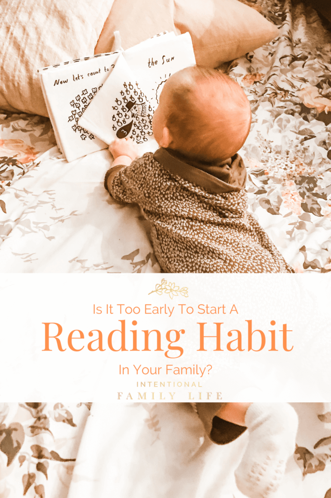 Image of baby on tummy in crib turning the page of a fabric baby book - concept of start good reading habits early