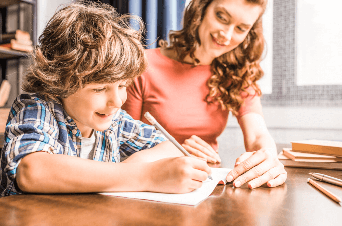mother and son working together on schoolwork; concept of how to start homeschooling