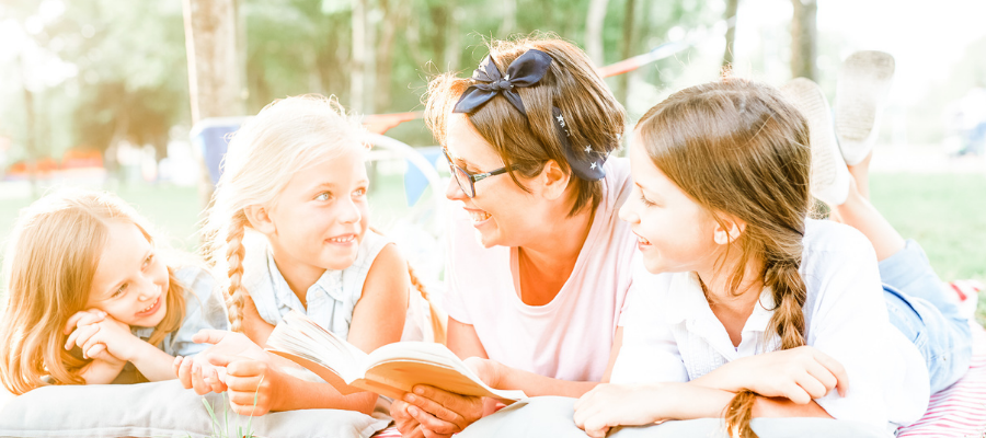 Happy mother and three pretty daughters reading outside in the sunshine - concept of read aloud books or books for summer